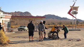 Backstage photo of crew filming car at gas station